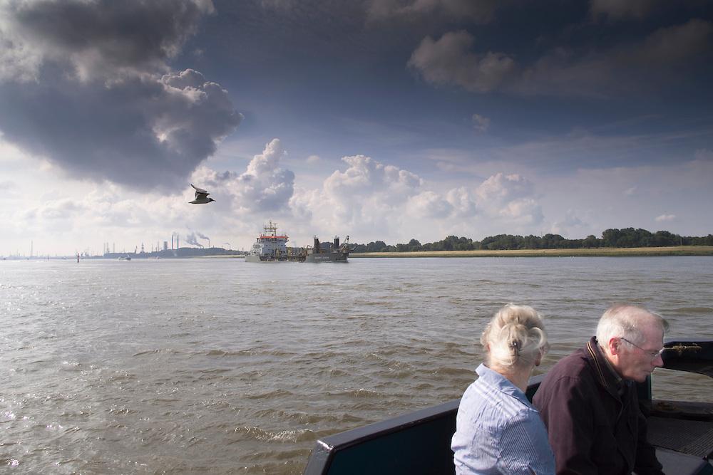 Twee ouderen kijken op de veerpot tussen Maassluis en Rozenburg naar het scheepvaartverkeer.<br /> <br /> Two elder people are watching the ships on a ferry between Maassluis en Rozenburg.