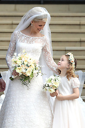 Newlywed Lady Gabriella Windsor with a young bridesmaid on the steps of the chapel with their bridesmaids, page boys and guests after their wedding at St George's Chapel in Windsor Castle.