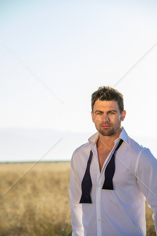 good looking man in a white shirt and loose tuxedo tie
