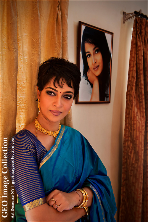Bengali actress Churni Ganguly stands near a picture of her as a young woman at home in South Calcutta, now formally called Kolkata.  She is considered one of the premier avant-garde actresses in India.