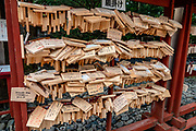 """Ema (""""picture-horse"""") are small wooden plaques, common to Japan, in which Shinto and Buddhist worshippers write prayers or wishes. The ema are left hanging up at the shrine, where the kami (spirits or gods) are believed to receive them. They often carry images or are shaped like animals, or symbols from the zodiac, Shinto, or the particular shrine or temple. In ancient times people would donate horses to the shrines for good favor; over time this was transferred to a wooden plaque with a picture of a horse. Once inscribed with a wish, Ema are hung at the shrine until they are ritually burned at special events, symbolic of the liberation of the wish from the writer. Toshogu Shrine is the final resting place of Tokugawa Ieyasu, the founder of the Tokugawa Shogunate that ruled Japan for over 250 years until 1868. Initially a relatively simple mausoleum, Toshogu was enlarged into the spectacular complex seen today by Ieyasu's grandson Iemitsu during the first half of the 1600s. Toshogu contains both Shinto and Buddhist elements, as was common until the Meiji Period when Shinto was deliberately separated from Buddhism. Toshogu is part of Shrines and Temples of Nikko UNESCO World Heritage site."""