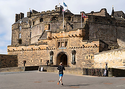 Edinburgh, Scotland, UK. 18 April 2020. Views of empty streets and members of the public outside on another Saturday during the coronavirus lockdown in Edinburgh. Esplanade of Edinburgh Castle is deserted with a few runners outside. . Iain Masterton/Alamy Live News