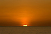 The sun sets on a cloudless ocean horizon on the island of Oahu, Hawaii
