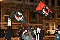 © Licensed to London News Pictures. 05/11/2017. London, UK. ANTIFA flags flying as Demonstrators Outside Downing Street take part in the Million Mask March, an anti-capitalist protest organised by Anonymous UK. The march takes place on Guy Fawkes Night, also known as bonfire night, the anniversary of the gunpowder plot to blow up the Houses of Parliament in London. Police have announced a series of restriction in an attempt to control the event. Photo credit: Ben Cawthra/LNP