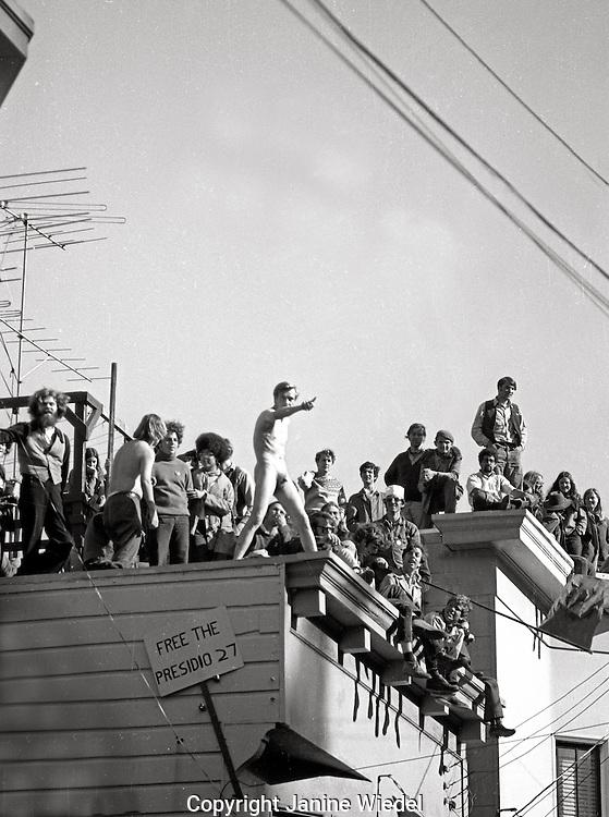 Berkeley students on rooftops watching the riots below. Earlier James Rector, a bystander had been shot observing from another roof, Berkeley California 1969