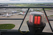 Aerial view (with control tower lighting) showing expanse of airport land with airliners at London Heathrow.