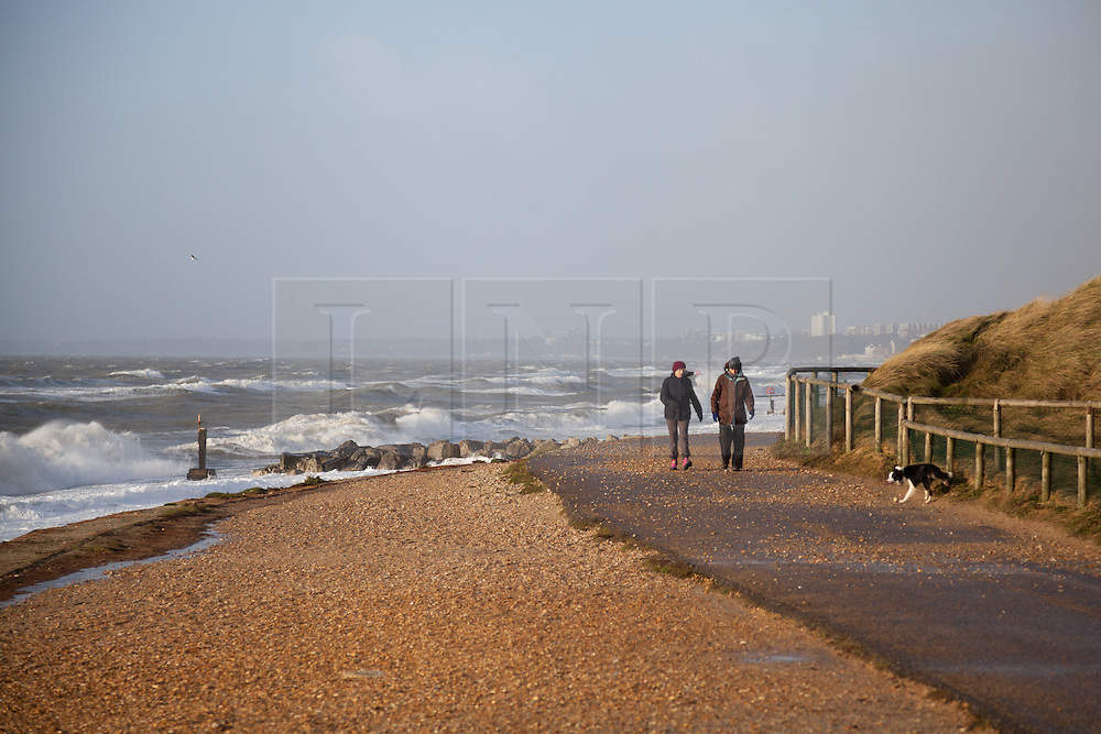 © Licensed to London News Pictures. 06/01/2014. Hengistbury Head, Christchurch, Dorset, UK. Dog walkers walk along the sea front as waves roll in from the English Channel and crash against the breakwaters near the beach between Boscombe and Hengistbury Head near Christchurch in Dorset. Dorset is expected to be one of the worst affect areas, with more heavy rain and flooding forecast. Photo credit : Rob Arnold/LNP