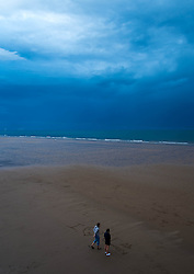 © Licensed to London News Pictures. <br /> 08/06/2014. <br /> <br /> Saltburn, United Kingdom<br /> <br /> A couple write in the sand as dark and brooding thunder clouds form over Teesside.<br /> <br /> Photo credit : Ian Forsyth/LNP