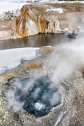 Small hot spring in the Upper Geyser Basin in Yellowstone National Park.   Another spring across the Firehole River is hosting some pretty thermophile bacteria.