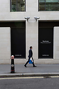 A Londoner walks beneath two CCTV cameras in the City of London, one of the most-watched cities in the world, on 11th August, 2017, in London, England. According to 2011 figures, there are 420,000 CCTV cameras in London.
