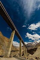 New elevated section of the The Karakoram Highway passing through the Pamir Mountains in Xinjiang China. It is the highest paved international road in the world; it connects Western China and Pakistan. It is one of the very few routes that cross the Himalayas and the most westerly of them. Historically, this was a caravan trail, one branch of the ancient Silk Road.
