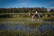 2015/03/03 – Monte Maiz, Argentina: Daniel, a farmer in the Monte Maiz region rifes his horse on a path now-a-days covered with water. Floods are really common nowadays in the region, because the soil can't absorb much water since pestifies make it harder and less absorvent. Another reason is that soy needs less water than other crops, so the water under the soil its just a mere 30cm from the surface making floods common when rain falls. (Eduardo Leal)
