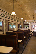 Manze's Eel, Pie and Mash shop in Walthamstow, East London, UK.Although the shop still trades under the original Manze name, it is now independently owned and no longer part of the Manze family. This resturant is a Grade-2 listed building with antique pressed-tin tiles on the ceiling.Eel, pie and mash shops are a traditional but dying business. Changing tastes and the scarcity of the eel has meant that the number of shops selling this traditional working class food has declined to just a handful mostly in east London. The shops were originally owned by one or two families with the earliest recorded, Manze's on Tower Bridge Road being the oldest surviving dating from 1908. Generally eels are sold cold and jellied and the meat pie and mash potato covered in a green sauce called liquor.
