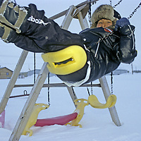 BAFFIN ISLAND, Nunavut, Canada. Inuit youngster plays outside on swing in sub-zero temperatures at Clyde River.