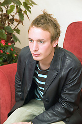 Young man sitting on a sofa; looking worried,