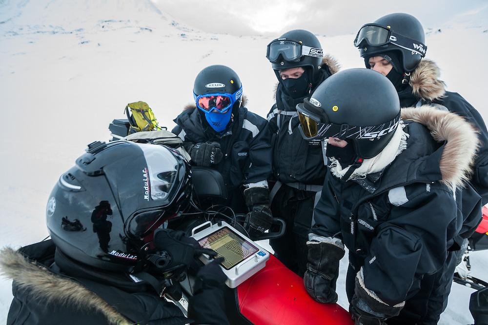 Heïdi Sevestre (left) helps UNIS students interpret the results of a practice snowmobile depth-sounding radar survey on Tellbreen, Svalbard.