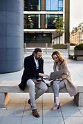 Businessman and woman sat outside corporate offices on a bench, working together on a laptop in St Helier,. Jersey, CI