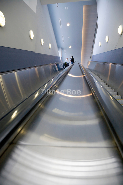 people descending a very long escalator