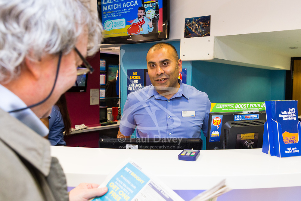 Betting Shop Manager-of-the-Year finalist Amran Al-Haque talks to one of his customers at Coral, 1 Canada Square, Canary Wharf, London, November 08 2018.