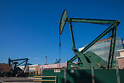 Oil well and pumpjacks in parking lot of a restaurant in the City of Signal Hill. Once a massive oil producing area, oil wells are still mixed in its now residential neighborhoods. Los Angeles Coutny, California, USA