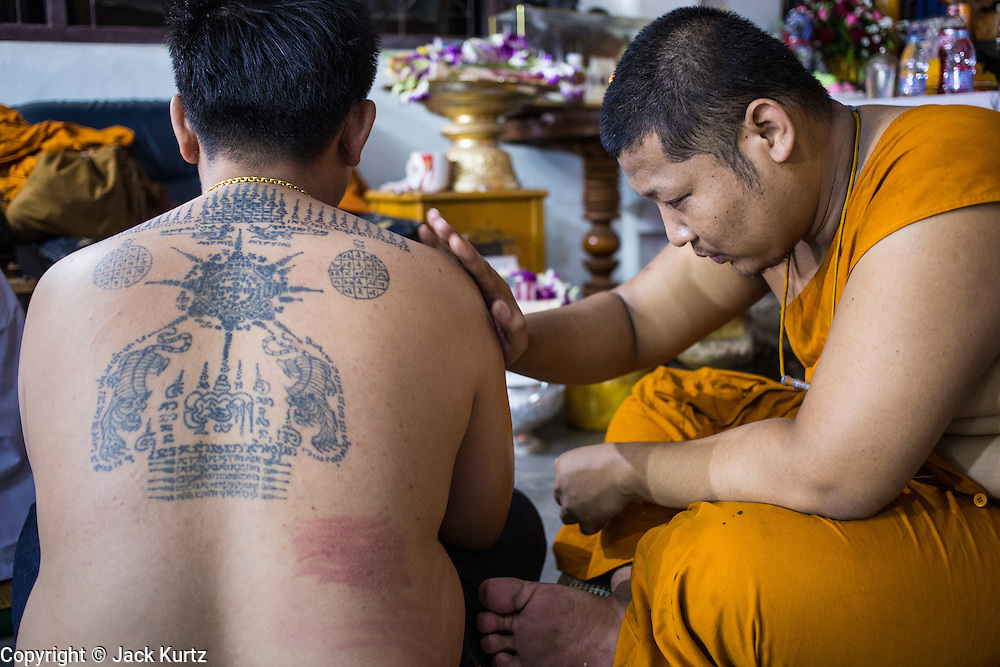 """22 MARCH 2013 - NAKHON CHAI SI, NAKHON PATHOM, THAILAND: A monk blesses a man's new Sak Yant tattoo at Wat Bang Phra during the tattoo festival. Wat Bang Phra is the best known """"Sak Yant"""" tattoo temple in Thailand. It's located in Nakhon Pathom province, about 40 miles from Bangkok. The tattoos are given with hollow stainless steel needles and are thought to possess magical powers of protection. The tattoos, which are given by Buddhist monks, are popular with soldiers, policeman and gangsters, people who generally live in harm's way. The tattoo must be activated to remain powerful and the annual Wai Khru Ceremony (tattoo festival) at the temple draws thousands of devotees who come to the temple to activate or renew the tattoos. People go into trance like states and then assume the personality of their tattoo, so people with tiger tattoos assume the personality of a tiger, people with monkey tattoos take on the personality of a monkey and so on. In recent years the tattoo festival has become popular with tourists who make the trip to Nakorn Pathom province to see a side of """"exotic"""" Thailand. The 2013 tattoo festival was on March 23.    PHOTO BY JACK KURTZ"""