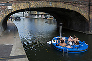 Women float along the cold waters of the Regents Canal in a hot tub from the company HotTug, on 22nd October, in London, England. The HotTug is a design by Frank de Bruijn, who works on a barge in the port of Rotterdam. It's constructed from wood and fitted with glass-fibre reinforced polyester and is powered by a built-in electric motor so is very quiet.