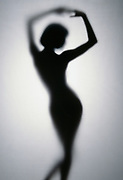Graceful nude woman in silhouette with shadows behind translucent matte material