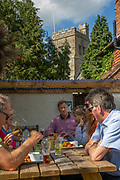 A group of people sit around a table and eat lunch outside the The Flying Horse Pub, Cage Land, Smarden, Kent, England, UK.  (photo by Andrew Aitchison / In pictures via Getty Images)