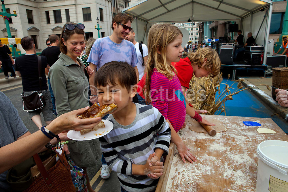 Boy eating a sandwich while learning to bake with Brockwell Bake's mobile bakery †and artisan baker Vincent Talleu on Southwark Bridge which is transformed into a giant banqueting space, designed by Cathy Wren, with visitors invited to share a meal, to eat, drink, dance and make merry..The Thames Festival celebrates London and the iconic river at its heart - the Thames - by dancing in the streets, feasting on bridges, racing on the river and playing at the water's edge..