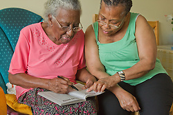 Carer and elderly visually impaired woman solving crossword.