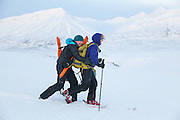 Kiya Riverman hitches a ride on the back of Mylène Jacquemart's skis in Foxdalen, Svalbard.