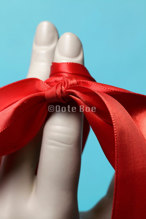 red ribbon tied around female mannequin finger