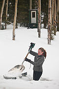 Sarah Conlin shovels snow into melting pans for drinking water outside the backcountry North Pole Hut, San Juan Mountains, Colorado.