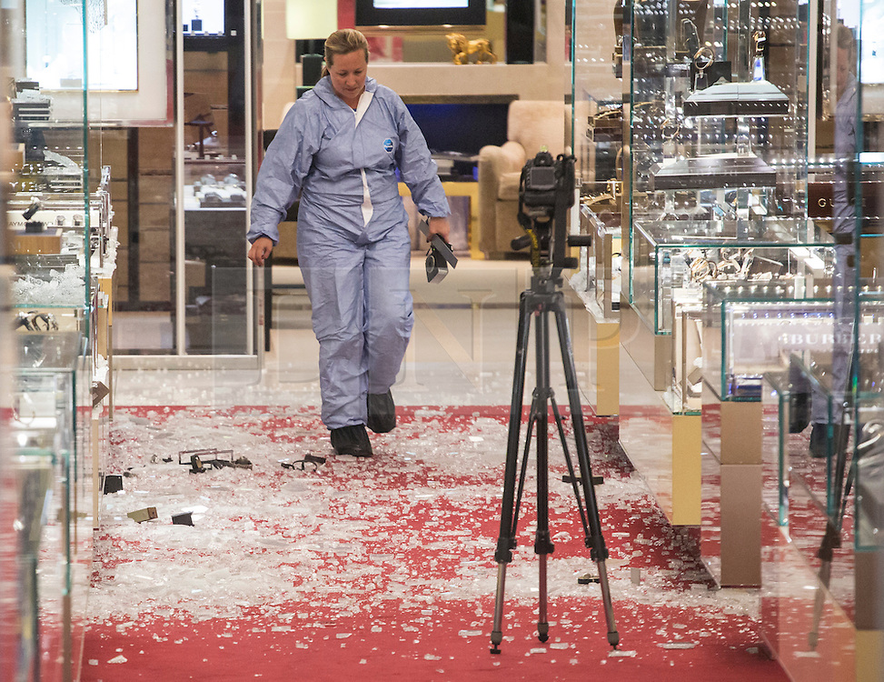 © licensed to London News Pictures. London, UK 06/06/2013. A forensic officer investigating the damage left after an armed robbery at Selfridges on Oxford Street, London. Photo credit: Tolga Akmen/LNP