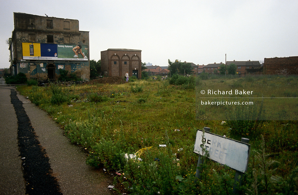 A solitary person walks over wasteland in Liverpool, England, left after housing was demolished decades ago - its impoverished population having moved out for a better life elsewhere. the sign tells us the name of this road but paint has been daubed over it in an attempt perhaps, to erase its identity now that the community has gone too. Billboards for consumer goods are on show for  non-existent shoppers.