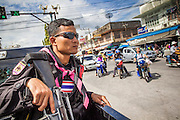 31 OCTOBER 2012 - YALA, YALA, THAILAND:  A Thai soldier on security detail for the villagers from Wat Kohwai on their Ok Phanso procession watches the streets of Yala as they enter the city. Ok Phansa marks the end of the Buddhist 'Lent' and falls on the full moon of the eleventh lunar month (October). It's a day of joyful celebration and merit-making. For the members of Wat Kohwai, in Yarang District of Pattani, it was a even more special because it was the first time in eight years they've been able to celebrate Ok Phansa. The Buddhist community is surrounded by Muslim villages and it's been too dangerous to hold the boisterous celebration because of the Muslim insurgency that is very active in this area. This the year the Thai army sent a special group of soldiers to secure the village and accompany the villagers on their procession to Yala, a city  about 20 miles away.  PHOTO BY JACK KURTZ