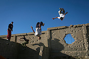 The Gaza Parkour And Free Running team practice in a cemetery on the outskirts of their refugee camp in Khan Younis, Gaza. The walls show damage from past Israeli incursions.