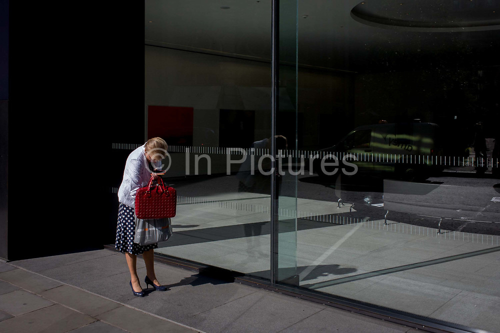 A woman searches at the bottom of her bag in front of an office foyer window in the City of London, the capital's financial district and oldest quarter. As if forgetful, the lady puts her hand deep into the bag and fishes around for whatever item is missing. With her phone in one hand and standing in autumn sunshine, she is near the corporate floor space in Threadneedle Street, near the Bank of England. Reflected light stretches into the otherwise shadowy recess of the building where visitors seating is carefully positioned.