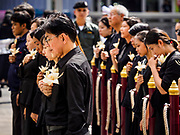 26 OCTOBER 2017 - BANGKOK, THAILAND:  Thais in mourning clothes hold their sandalwood flowers over their hearts while they wait to make offerings during the funeral ceremony for Bhumibol Adulyadej, the Late King of Thailand. The king died on 13 October 2016 and was cremated 26 October 2017, after a mourning period of just over one year. The revered monarch was the longest reigning king in Thai history and is credited with guiding Thailand through the turbulent latter half of the 20th century.  PHOTO BY JACK KURTZ