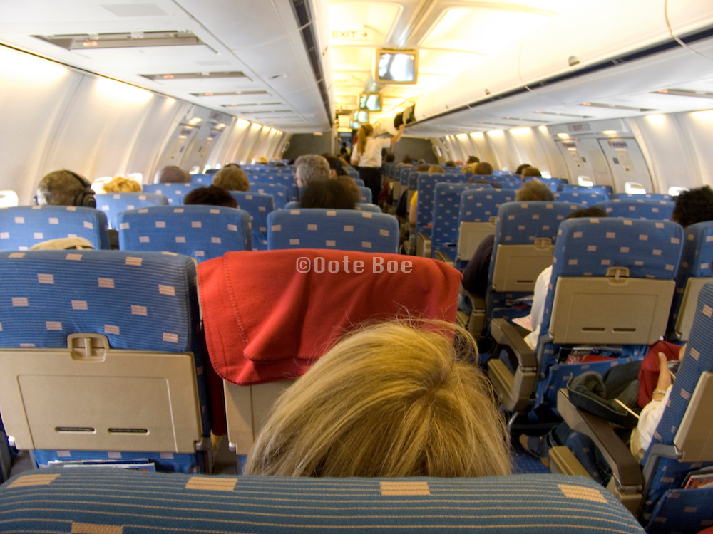 stewardess closing the overhead compartment before taking off