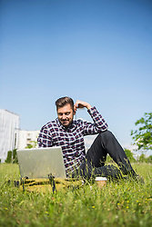 Young man working on laptop and sitting in park, Munich, Bavaria, Germany
