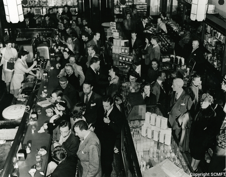 1945 Schwab's Drug Store. Singer Dick Haymes has his hands on Sidney Skolsky's shoulders (center of photo)
