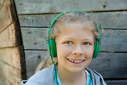 Girl listening music with headphones in playground, Munich, Bavaria, Germany