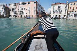 Gondolier of public ferry Traghetto gondola crossing the Grand Canal in Venice