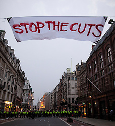 """© under license to London News Pictures. 25/03/2011: After police cleared Piccadilly of protesters, a large banner remains suspended across Piccadilly, hung by protesters demanding a stop to cuts. Credit should read """"Joel Goodman/London News Pictures""""."""