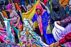 Uyghur women shop clothes at market in Khotan, Xinjiang province in China.