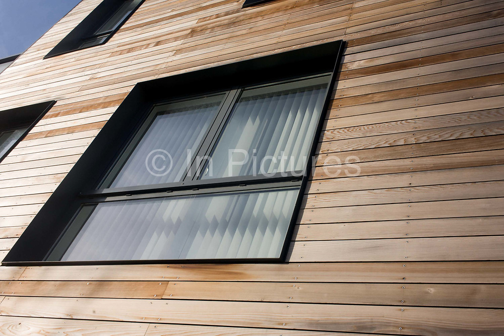 We look upwards to wooden panels on exterior walls of modern apartments overlooking the Thames on the Greenwich Peninsular, Bermondsey. The modern frames in aluminium material are angular, their right-angles cornered perfectly and set in the strips of clean and smooth timber. Sets of screws or rivets hold the outer facade in place to make this fine building situated on the river Thames in the UK capital. Greenwich Peninsula is one of the UK's largest regeneration projects covering 190 acres. In partnership with the Greater London Authority and The Royal Borough of Greenwich, we are creating a new district for London including homes, offices, schools, shops and community facilities.