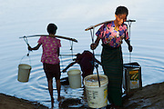 Village woman collecting water from reservoir at sunset