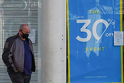 © Licensed to London News Pictures. 27//11/2020. Sheffield, UK. A shopper wears a face mask walks past   a sale sign in the shop window of Dorothy Perkins in Sheffield city centre. Photo credit: Ioannis Alexopoulos/LNP