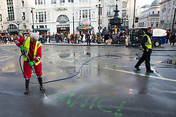 London, UK. 15th April 2019. A street cleaner removes graffiti daubed on the road by climate campaigners from Extinction Rebellion at Piccadilly Circus during the first day of 'International Rebellion UK - Shut Down London!' events to call on the Government to take urgent action to address climate change.